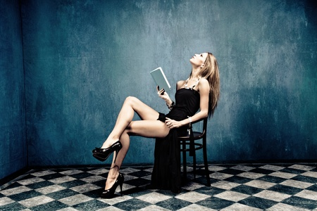 tacones: rubia sensual vestido negro y tacones altos sentado en una silla con un libro en la sala vac�a