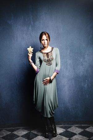peacefull: young woman in oriental dress holding flower orchid in hand, indoor shot