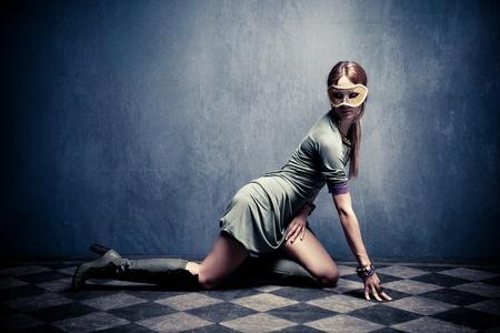 kneel: beautiful woman with carnival mask posing on floor,  full body shot, indoor shot Stock Photo