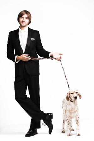 handsome  young  man in tuxedo and his dog, studio shot photo