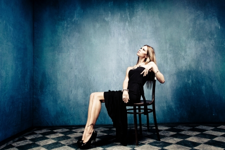 high fashion: blond woman sit in empty room in elegant black dress and high heels