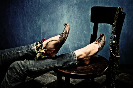 female legs in blue jeans and oriental footwear leaned on chair, indoor shot photo