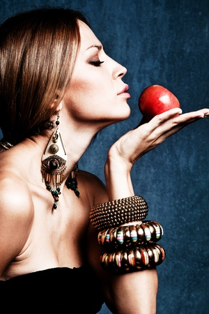 woman with oriental jewelry hold an apple, profile, studio shot Stock Photo - 11313767