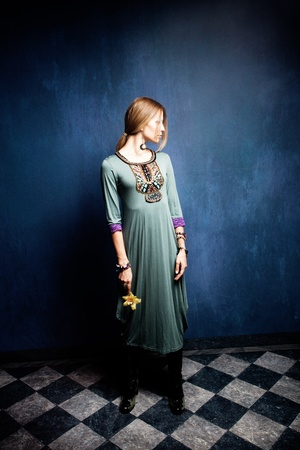 woman in long dress stand in empty room hold orchid in one hand photo