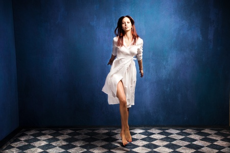beautiful barefoot woman in white dress in motion in empty room  photo