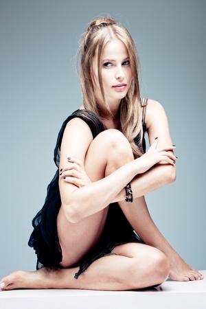 plan éloigné: blonde femme à la mode aux pieds nus, tourné en studio, coup complet du corps, assis Banque d'images
