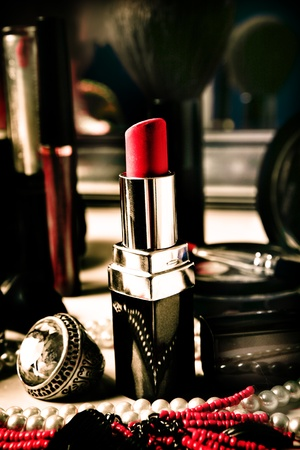 red lipstick and jewelry on dressing table photo