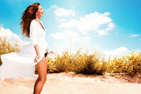 female body: smiling woman in white dress and bikini standing on beach, sunny summer day