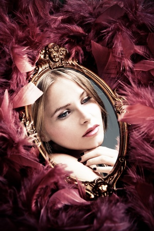 woman mirror: beautiful young woman reflection in mirror surrounded by plumage