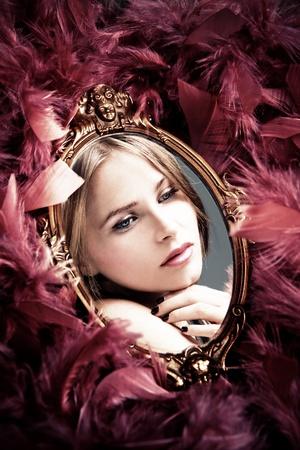 piume: bella riflessione giovane donna nello specchio circondato da piumaggio