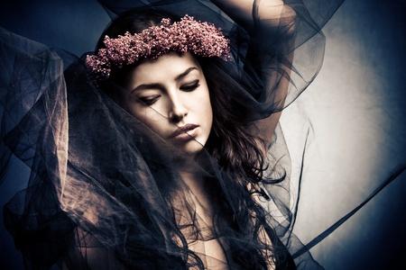 pohanský: žena v tanečním pohybu pod černým závojem s věncem květin ve vlasech