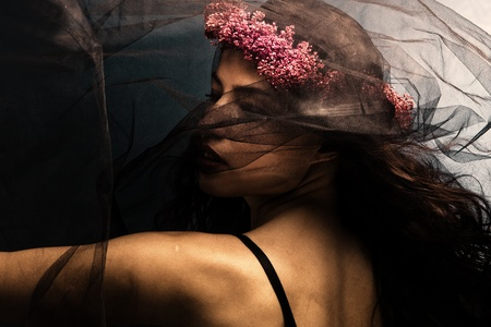 pagan: woman in dancing motion  under black veil with wreath of flowers in hair Stock Photo