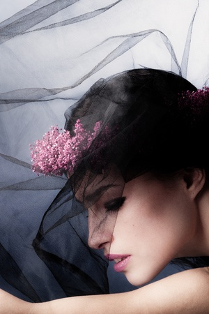 stylish beauty portrait of a woman under black veil with wreath of flowers in hair photo