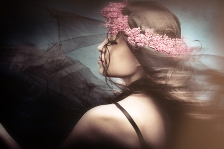 beautiful woman dancing with black veil and wreath of flowers in hair photo