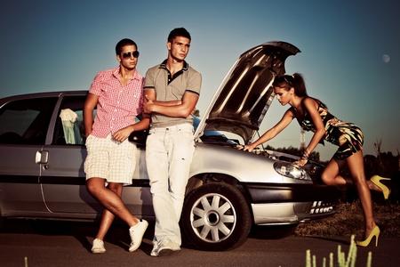 in trouble: chica de fijaci�n del motor coche, mientras que dos de los hombres j�venes que esperaban en el coche