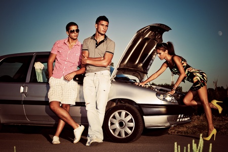 car trouble: girl fixing car engine while couple of young man waiting by the car Stock Photo