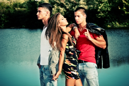 lean on hands: young woman with two young man, love triangle, outdoors shot Stock Photo