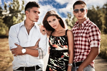men and women: young woman with two young man, love triangle, outdoors shot Stock Photo