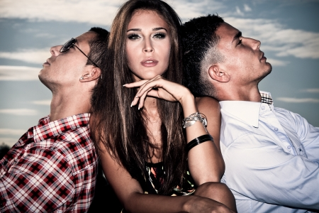 man outdoors: one young woman and two young men, love triangle, outdoors shot