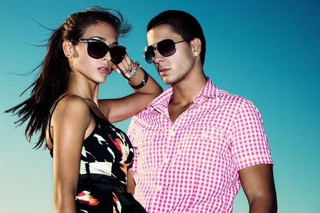 young couple with sunglasses outdoors shot against blue sky photo