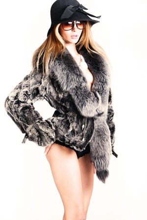 young woman wearing fur, hat and sunglasses, retro style, studio shot photo
