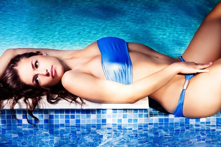 tanned body: woman in blue bikini lie by the pool, summer day