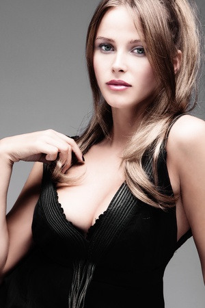 decolletage: elegant young woman in provocative dress, studio shot