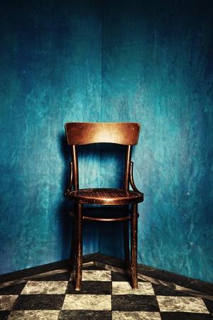 silla de madera: silla de madera en la esquina de la sala de grunge con paredes azules y piso de baldosas