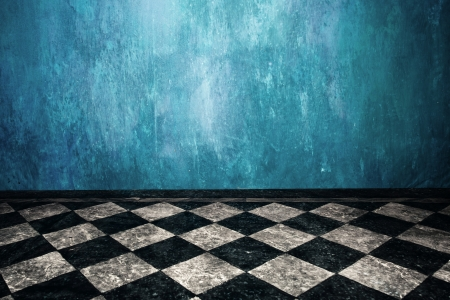 gothic design: grunge blue wall and tiled floor in empty room