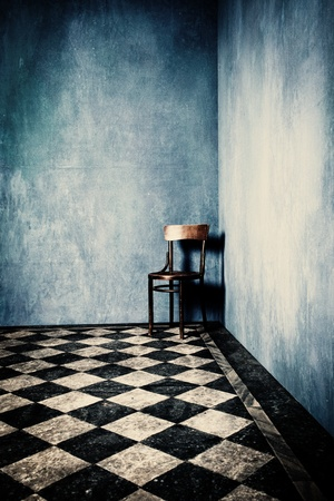 abandoned room: grunge room with blue old walls tiled floor and wooden chair in corner
