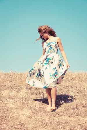 young woman barefoot in silk dress on top of the hill  sky in background, retro colours, grain added photo