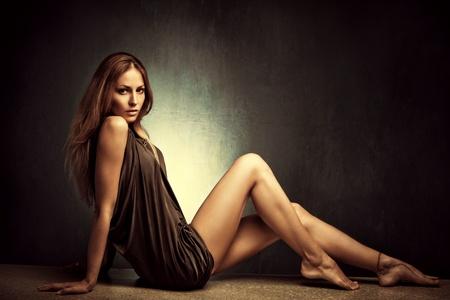 mooie vrouwen: jonge vrouw in elegante korte jurk zitten op blote voeten, full body shot, studio-opname Stockfoto