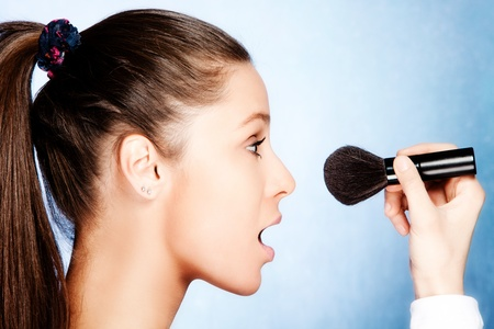 teen girl  apply powder with cosmetic brush, profile, studio shot