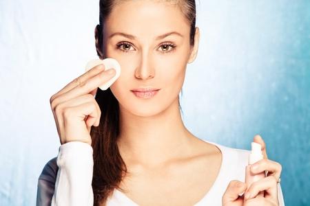 mujer maquillandose: mujer joven aplicar la base con el aplicador de esponja, tiro del estudio
