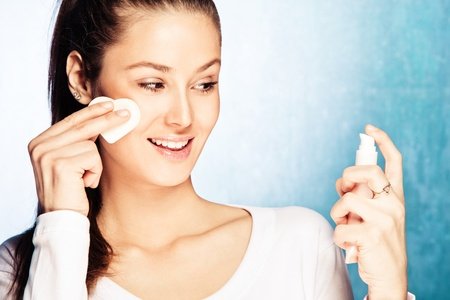 toner: young smiling woman apply foundation with sponge applicator, studio shot