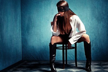 sensual young woman with lace covering eyes sit on chair in shirt and leather boots photo