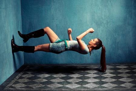 levitacion: una mujer con botas y pantalones cortos vaqueros subir la pared en la habitaci�n sucia