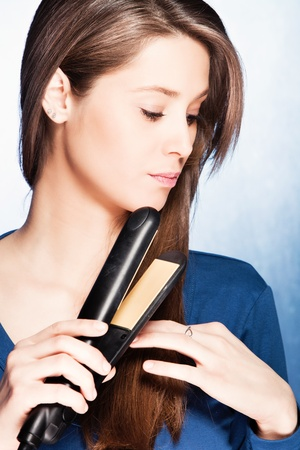 young woman use hair straightener iron, studio shot photo