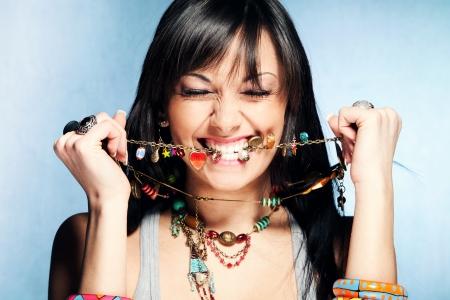 trinkets: pretty dandy young woman bite her necklace, studio shot