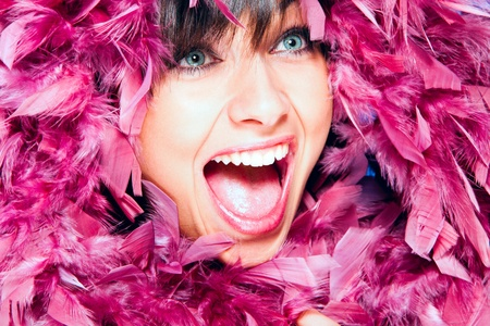 cheerfull: cheerfull smiling woman in pink feather portrait, studio shot