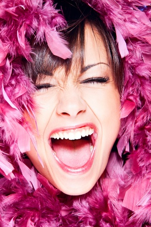 screaming cheerful woman in pink feathers portrait, studio shot photo
