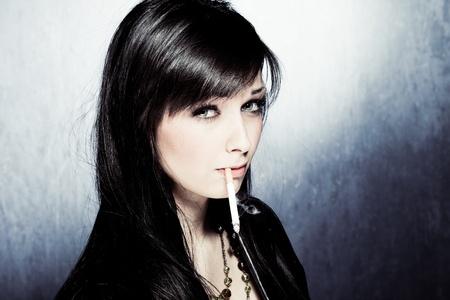 black hair blue eyes: black hair woman in leather jacket, smoking, studio shot Stock Photo