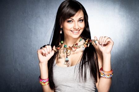 mujer bonita muestra su collar con colgantes de colores