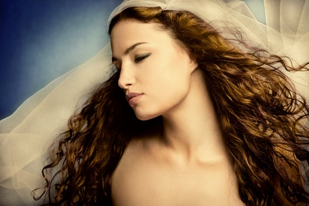young woman with veil, long curly hair, eyes closed, head in profile, small amount of grain added photo