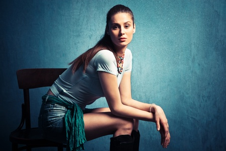 nonchalant: young nonchalant woman in shorts and t-shirt sit in empty room on old chair  Stock Photo