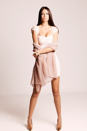 elegant young woman in short dress and high heels, studio shot photo