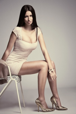amount: elegant young woman in short dress, high heels, sit on chair, studio shot, small amount of grain added