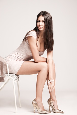 elegant young woman in short dress and high heels, studio shot photo