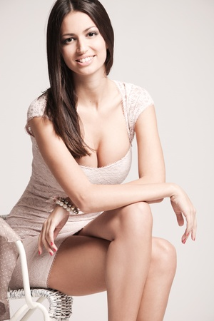 elegant smiling young woman in short dress  studio shot photo