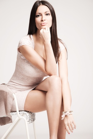 elegant young woman in short dress,  sit on chair, studio shot photo